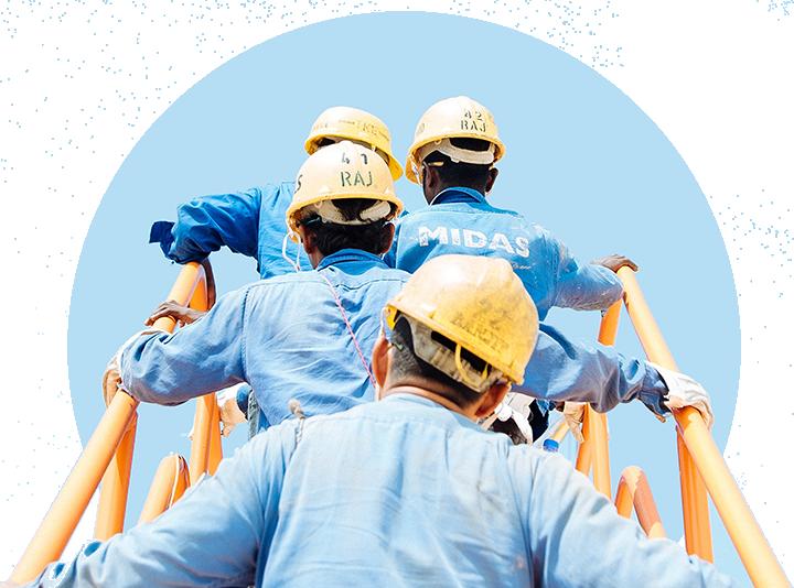 Photo of men yellow helmets climbing a construction site ladder