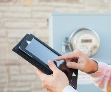 Photo of man in front of energy meter with ipad.
