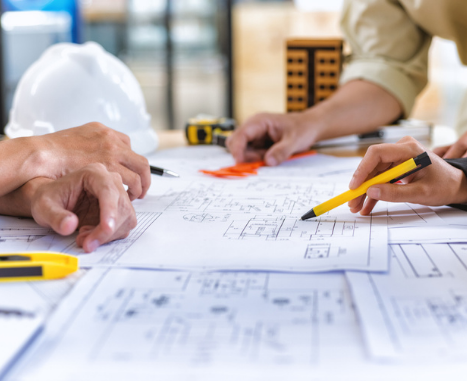 Three people review construction site plans.