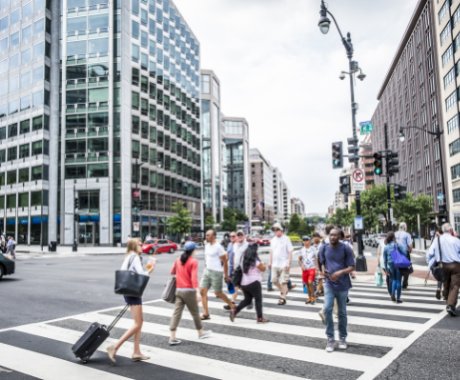 Photo of people crossing a busy street in downtown Washington, DC.