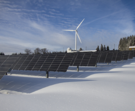 Solar panels and wind turbine on sunny day with snow