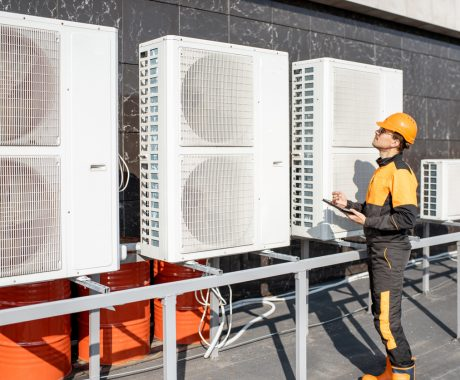 Professional workman in protective clothing adjusting the outdoor unit of the air conditioner or heat pump with digital tablet
